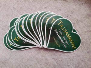 """Syntolkning: Klistermärken med ett grönt hjärta med texten """"Tillsammans för en mänskligare Försäkringskassa"""" #mänskligareFK"""